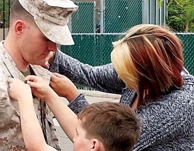 Jordan's wife, Jennifer, and son, Jay, pin on his medals following his recovery.  Courtesy photo