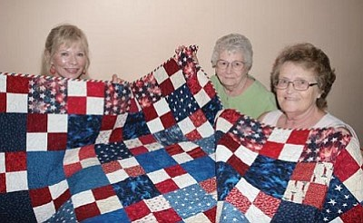VVN/Bill Helm<br> Jeannette Teets, Peg Miller and Jeanett Salyers, from left, show one of the patriotic quilts they made that will be on display at the Fort Verde Days inaugural Creator Faire. The ladies will have a display at Creator Faire.