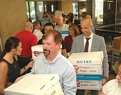 Volunteers deliver boxes Wednesday containing petitions with more than 146,000 signatures designed to force a public vote on a legislatively approved plan to alter various election laws.  (Capitol Media Services photo by Howard Fischer)