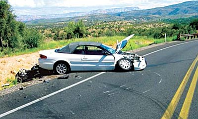 Both vehicles pictured at the point of rest after the crash with the motorcycle partially beneath the rear bumper of the convertible sedan. Courtesy photo