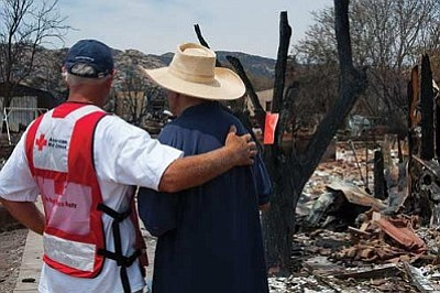 American Red Cross volunteer Marty Martindale gives some encouragement to Yarnell resident Gene Criner, one of scores who lost homes in the wildfire that killed 19 Granite Mountain Hotshot firefighters on June 30. (Photo by Todd Tamcsin/courtesy American Red Cross)