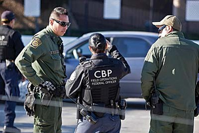 Border Patrol agents and a Customs and Border Protection field operations officer talk at a border crossing in San Ysidro, Calif. (Photo by Josh Denmark/courtesy CBP)