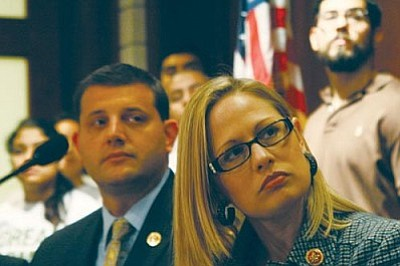 Rep. Kyrsten Sinema, D-Phoenix, listens during a news conference for a bill that she co-sponsored, which would make it possible to undocumented immigrants in this country to join the military. (Cronkite News Service photo by Pei Li)