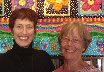 Anne Uruburu, left, of the Red Rock Quilters, congratulates Sharon Elaine, winner of the quilt raffle at SPL-V.