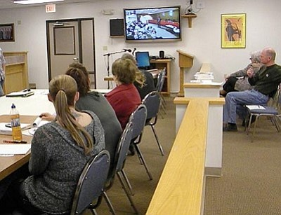Brandon Bonney speaks in Prescott (on screen) while the Cottonwood audience watches.