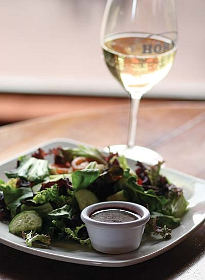 Peggy Fuller, executive chef at The Horn restaurant in Camp Verde, says that pairing wine with food works as easily for vegetarians as it does for meat-eaters. Pictured, The Horn's garden house salad with a cabernet vinaigrette dressing, served with a glass of Arizona Stronghold Tazi wine. VVN/Bill Helm