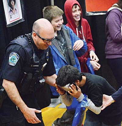 "Officer Dobrinski helps kids maintain their balance while they wear ""drunk goggles"" at Teen Maze."