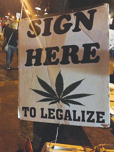 A sign seeks signatures on a petition to have a referendum in November on legalizing the recreational use of marijuana in Arizona. (Cronkite News Service Photo by Moriah Costa)