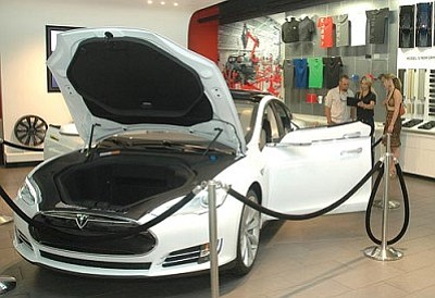 Would-be shoppers check out the all-electric Tesla at the company's Scottsdale showroom where, under current law, they cannot actually buy the vehicle. Legislation approved Wednesday by a Senate panel would let the company sell directly to consumers in Arizona. (Capitol Media Services file photo by Howard Fischer)