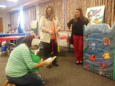 """Mayor Diane Joens and Susan Lacher of Verde Valley Healthy Families help 18-month old Matthew Evans """"fish for a book"""" at the Dr. Seuss family playgroup."""