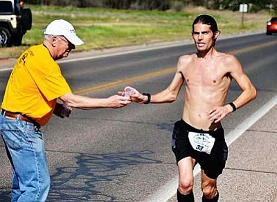 Gary Krugger, the overall marathon winner from Flagstaff, grabs a cup of water during the Brian Mickelsen marathon on April 12, 2014. Krugger completed his 26 miles in 2:48:02.50. VVN/Jon Pelletier
