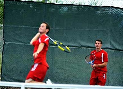 Tanner Caron watches doubles partner Gary Baker go up for a shot against Kingman High School. VVN/Travis Guy