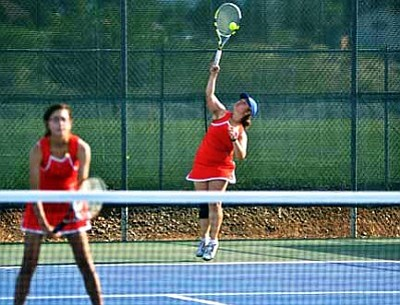 Senior Bethany Hickey launches a serve with her doubles partner Carol Curran waiting for the return. VVN/Travis Guy