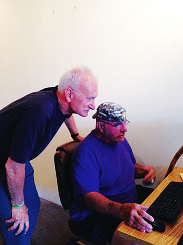 Library volunteer Thomas Hofmann (left) assists Michael Bosco with computer access.