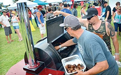 A huge smoker is used to cook meat by the Rub Your Meat BBQ team at the 9th Annual Rhythm and Ribs cook-off on Saturday. VVN/Vyto Starinskas