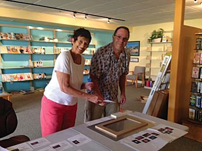 Anne Uruburu, chairperson of Rotating Artist Program, assists Mike Cadwell with his art installation at Sedona Public Library in the Village.