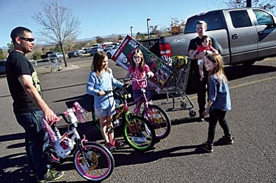 The Bevier family packs up their Friday deals in the Walmart parking lot in Cottonwood. Dad Nathan Bevier holds the bike belonging to 7-year-old Adrianne, right, sister Alexis, and Alexandria, both 9, are next to dad, and mom holds 10-month-old Angel. VVN/Vyto Starinskas