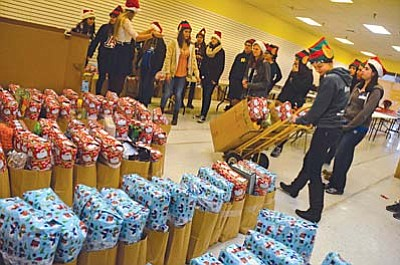 Mingus Union High School Senior Leah Mount uses a cart to roll out some of the 600 Giving Angels Christmas presents with other Mingus and Sedona High School students. VVN/Vyto Starinskas