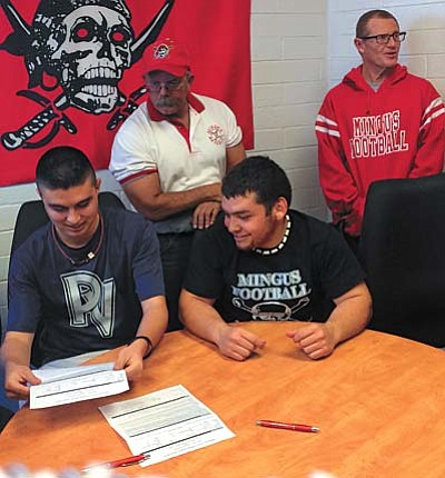 Tommy McCarty (left) and Orlando Machado (right) sign their letters of intent to play college baseball with coaches John Behlow and Bob Young in the background. VVN/Derek Evans