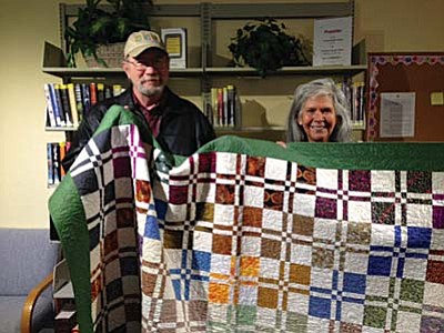 Dennis and Isabel Eilertson display the quilt chosen by quilt winner Elaine Lockwood.