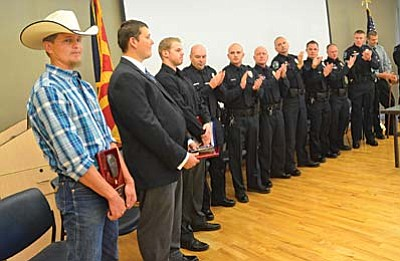 Cory Brady, Eric Fields, and Cole Taylor, far left to right, join the eight police officers at a recognition ceremony Wednesday after the three men were given awards for helping police officers in a brawl at the Cottonwood Walmart recently. VVN/Vyto Starinskas