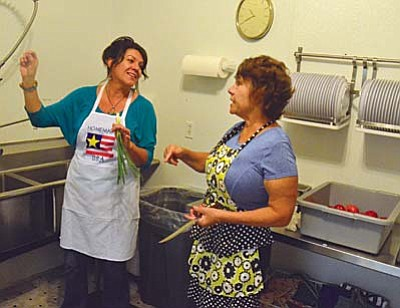 Jill Marie Sweet and Cheryl Saravo, volunteers at the Old Town Mission, cut up tomatoes and onions for tacos on Thursday. VVN/ Vyto Starinskas