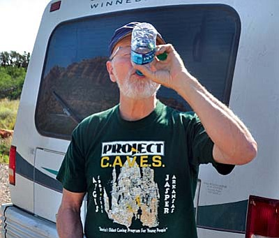 Rick Hinterthuer of Fayetteville, Ark., takes a drink of water and packs several more bottles in his backpack before hiking the Doe Mountain Trail in Sedona on Friday morning. VVN/Vyto Starinskas