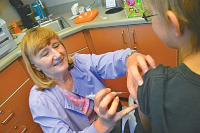 Public Health Nurse at the Yavapai Health Department Donna Metzler, RN, gives a vaccination shot to a student entering sixth grade at the health department offices in Cottonwood on Thursday. VVN photo by Vyto Starinskas