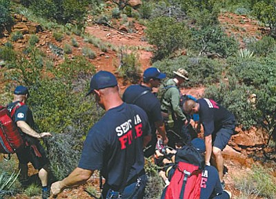 YCSO deputies help Sedona Fire personnel transport an injured hiker to an ambulance on July 19 after she had fallen off a cliff's edge on Bell Rock. YCSO photo
