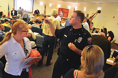 A police officer gives participants in the National monument proposal meeting at the Sedona Council Tuesday directions to seats. VVN/Vyto Starinskas