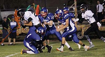 Trevor Heyer is assisted by teammates in bringing down a Pinon player during their game last Friday. Heyer brought down two interceptions and rush for a touchdown on Friday vs Monument Valley. (Photo by Greg Macafee)