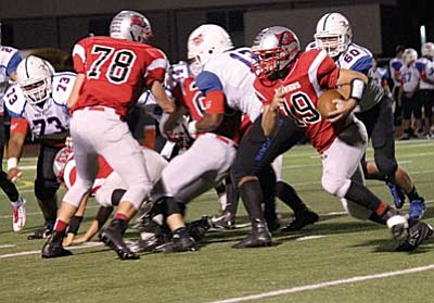 Trey Meyer rushes off the left side of his offensive line during the Mingus football game Friday night. Meyer took over under center in the second half, passing for two touchdowns as the Marauders went onto win 51-20 over the Moon Valley Rockets. (Photo by Greg Macafee)