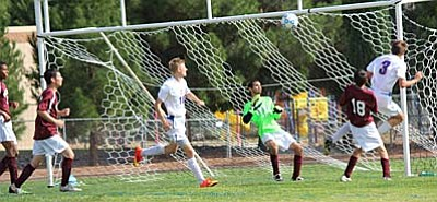 Wesley Loveall (#3) gets a head on the ball during a match up with Arizona Charter Academy this season while Nathan Schultz looks on. The boys team will face off with Phoenix Country Day on Thursday at 4 p.m. at PCD in the first round of the state playoffs. If the boys win they will take on snowflake in the second round of the state playoffs. (Photo by Greg Macafee)