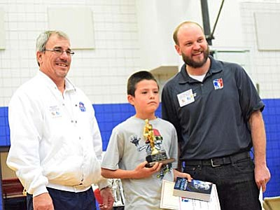 Jordan Fullmer, middle, poses with State of Arizona Hoop Shoot Chairman Gregg Boyce (Left)and Arizona North District Hoop Shoot Chairman Russel Hall (Right) after winning the 8-9 boys age group of the Elks Hoop Shoot competition held at Camp Verde Middle School this week. Fullmer will compete at the State competition at Apache Junction on February 13. (Photo by Greg Macafee)