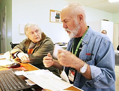 """Doug Forsyth, an AARP Foundation Tax-Aide volunteer, helps Camp Verde resident Mary Frost with her tax return recently. Before utilizing AARP, Frost, says it """"used to be a headache"""" to do her taxes. (Photo by Bill Helm)"""