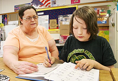 Angela Russell, fourth grade teacher at Clarkdale-Jerome School, helps Aiden Ashkar on the finer points of cursive writing. Aiden says he is pretty good with writing the letters e, n, i, t, r and c. (Photo by Bill Helm)