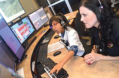 Jessica Casa and Communications Specialist and trainer Chelsea Shephard work the dispatcher's console at the Regional Communication Center in Cottonwood on Friday. Casa just reported that the Grinch is on the loose. VVN/Vyto Starinskas