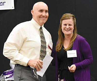 Mingus Union chemistry teacher Mike Westcott was named the 2016 Yavapai County Teacher of the Year Friday in Prescott. He is congratulated here by last year's winner, Larnell Sawyer. (Photo by Matt Hinshaw)