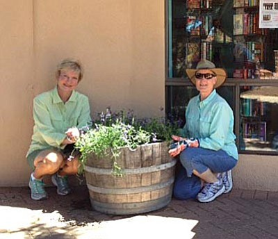 Jan Billiam, left,  and Juanita Peterson of the Sedona Area Garden Club tend to a planter at the Village library.