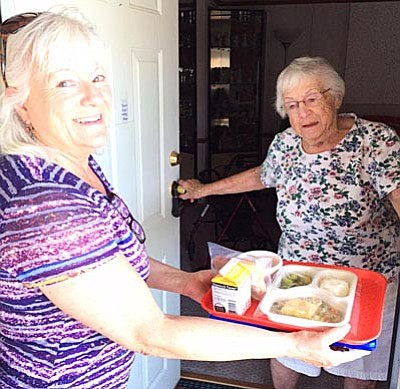 Volunteer Cyndi Collingwood, left, brings a meal to Alene Wood through the Meals-on-Wheels program. (VVN photo by Tom Tracey)