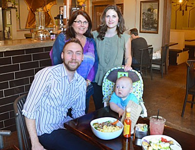 Pictured is Mine Café co-owner Joni Savage (l) and managers Kelsi Savage (r) and Mark Venker with infant son Dasch. (Photo by Vyto Starinskas)