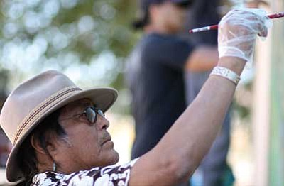 "Shonto Begay works on ""Sacred Hunt,"" a mural he and artist Cy Wagoner recently completed in Williams."