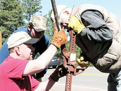 Lynda Duffy/WGCN<br> Joe Duffy, Richard Gianettino and Glenn Cornwell repair a fencepost at the Williams Cemetery on cleanup day in April.