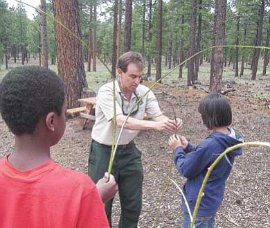 Photo/Jackie Banks<br> Archaeologist Neil Weintraub teaches kids how to make split-twig figurines, which are objects that archaeologists say Archaic hunters may have created to symbolize hunting success.