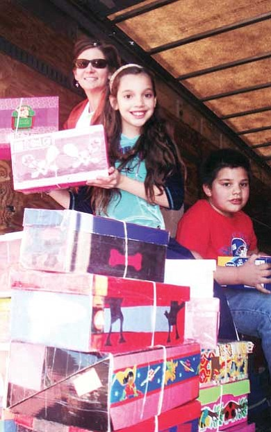 Katia and Michael Mendoza (right) help deliver packed shoeboxes to trucks waiting to transport them to a distribution center for Operation Christmas Child last year.