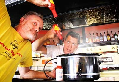Ryan Williams/WGCN<br> Chuck Vaughn, hot wings competition organizer, and Johnny Peasley perfect their wings recipe.