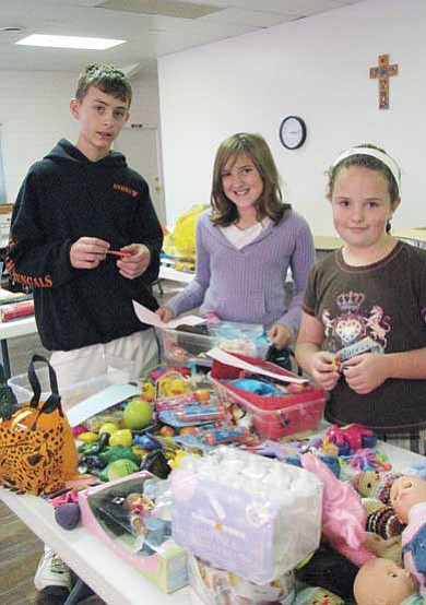 Lynda Duffy/WGCN<br> From left, Andrew Karlsberger, Kodie Hollamon and Alaina Karlsberger pack shoeboxes Oct. 16 during a community packing party. Packing parties will also be held 10 a.m.-4 p.m. Saturday and Oct. 30 at Walker Hall, Second and Grant. Assistance is very much needed and everyone is welcome.