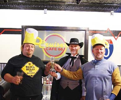 Submitted photo<br> Chuck Vaughn (center), organizer of the Wicked Wing Throw Down, presents a trophy to Steve Dryer  Oct. 30 at Cruiser's. The Dryer Brothers were selected  winners of the delicious contest.