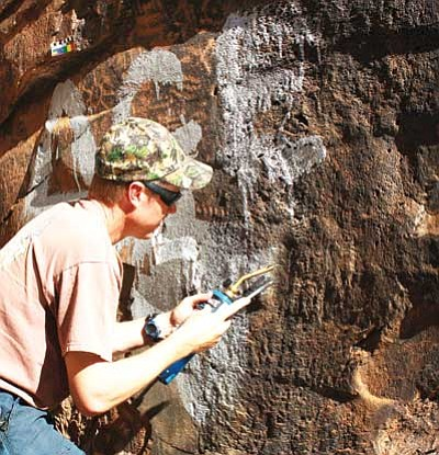 Photo/Kaibab National Forest<br> Kaibab firefighter PT Carter  applies heat to a fine steel brush to carefully remove paint outside of the petroglyphs.