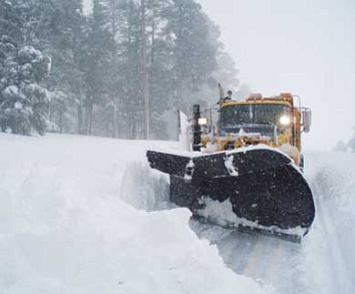 Photo/ADOT<br> An ADOT snowplow clears a road severly impacted by snowfall earlier this winter.